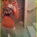 Miley Cyrus tomando una fotografia de su cuerpo casi desnudo